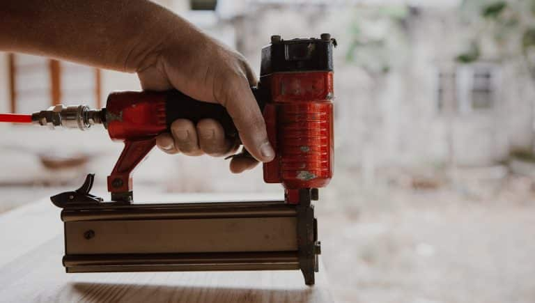 The carpenter is Making furniture the furniture .He is using a Staple gun to work.