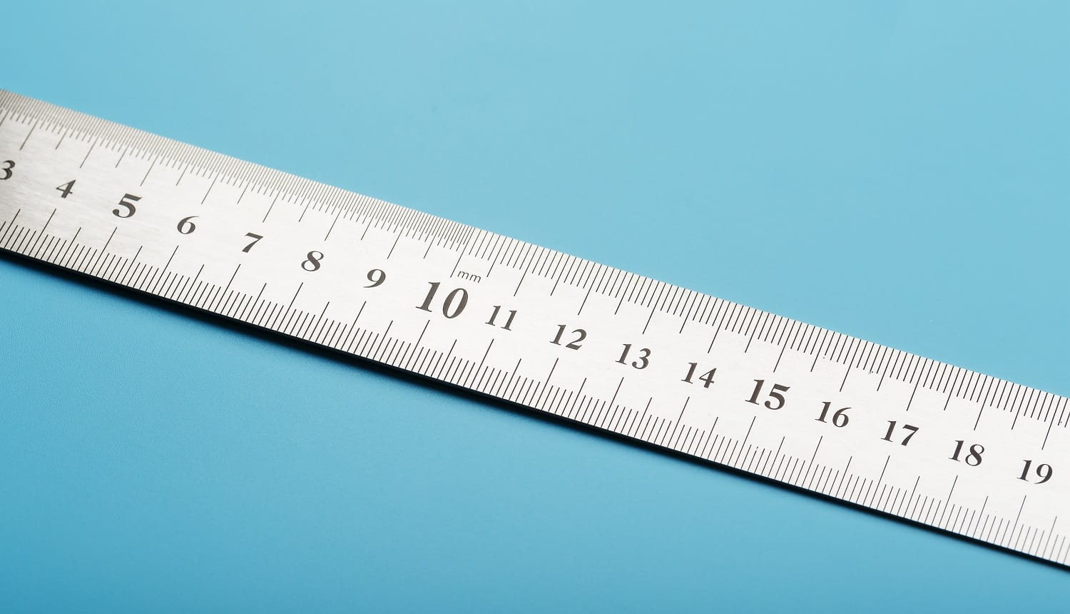 A metal ruler with a scale on a blue background is a superscape with a copy of the space for your text. Isolate