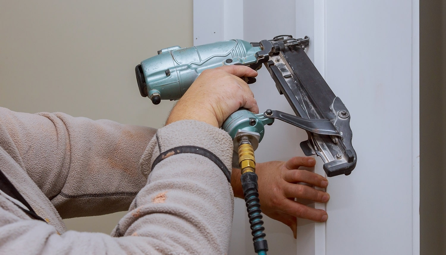 Construction handyman is working on renovation of apartment using air nail gun
