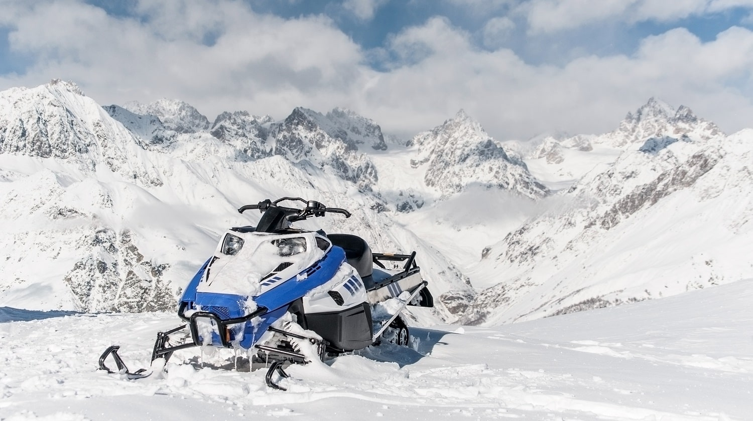 Modern blue snowmobile against the scenic background of high snow mountains peaks and cloudy sky
