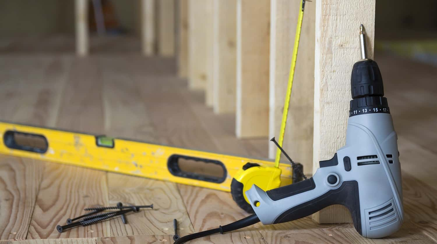 Close-up of professional tools: electrical screwdriver, level and measuring tape on background of wooden frame for future wall in attic room under reconstruction. Renovation and improvement concept.