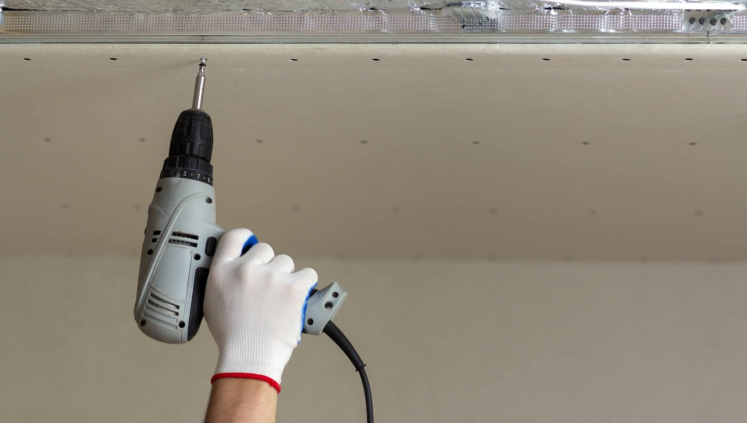 Close-up of constructor worker hand in protective glove with electrical cordless screwdriver connecting suspended drywall ceiling to metal frame. Renovation, construction and DIY concept.