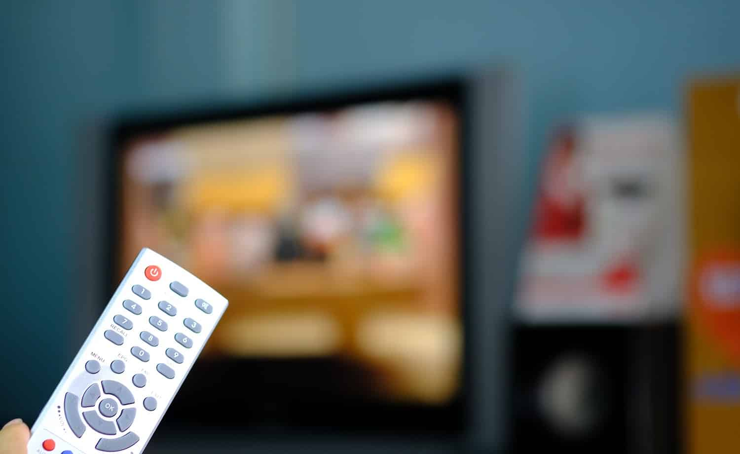 remote control satellite receiver holdig in hand for change channel blurred television background.