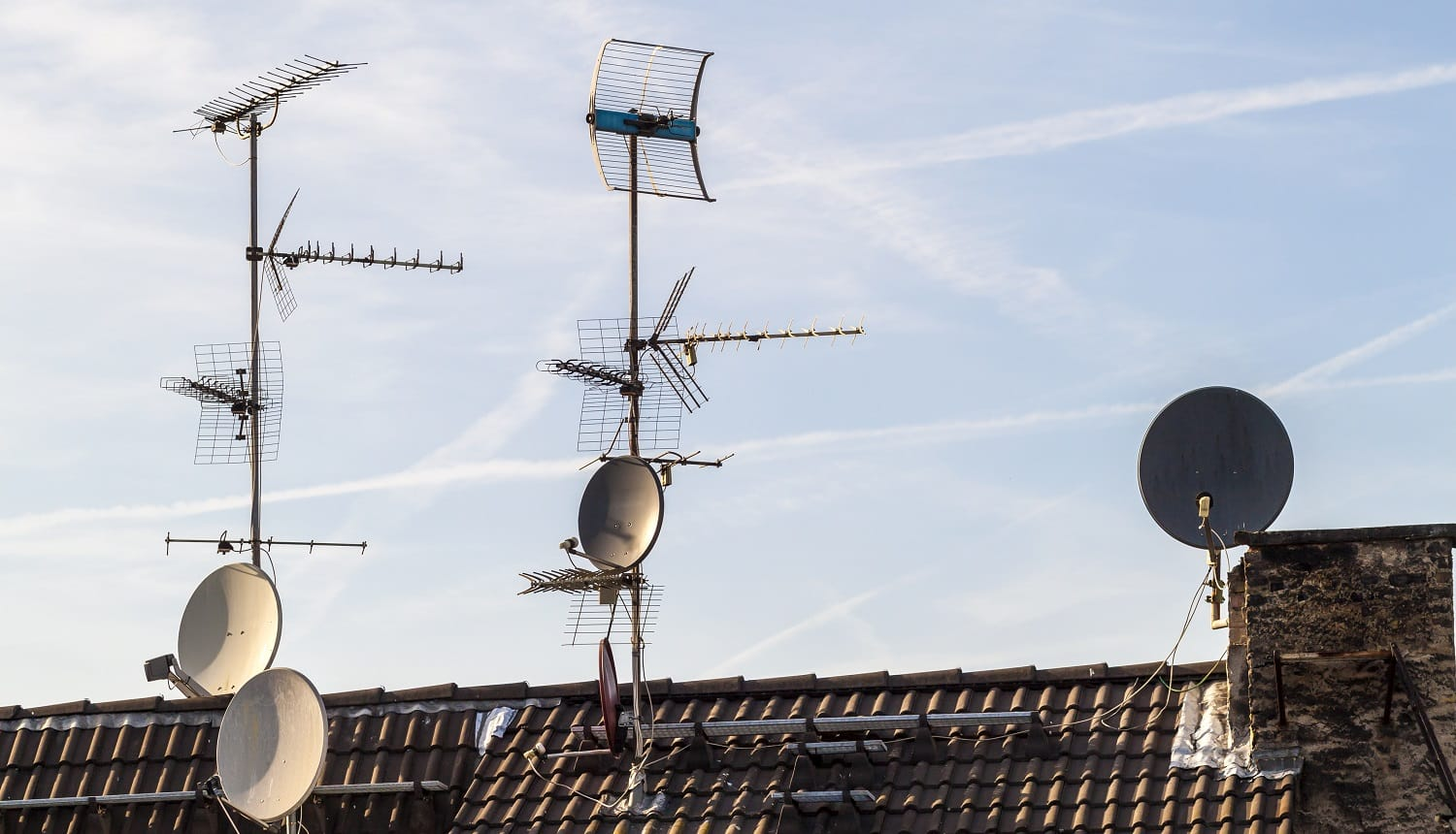 Old building roof with many different type receiver telecommunication antennas