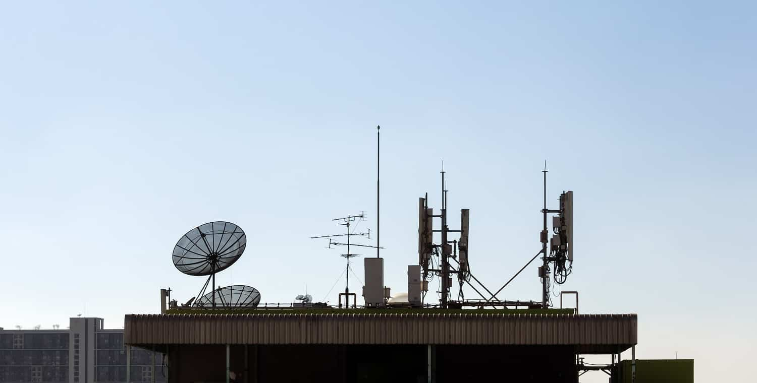 A group of telecomunication antenna and satellite dish on the roof of building with blue sky background