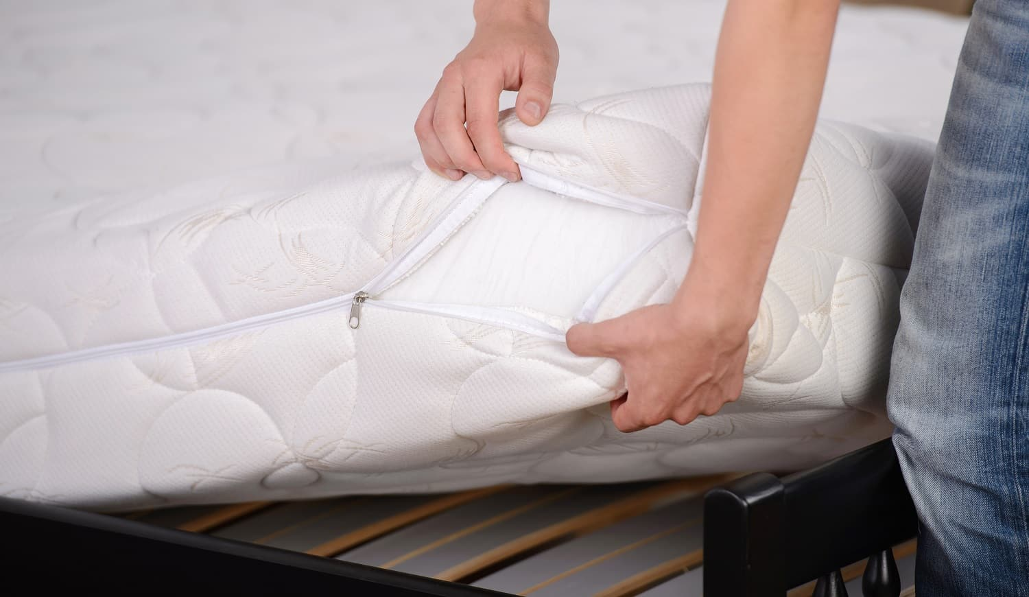 Man holding demonstrations quality mattress in the bedroom.