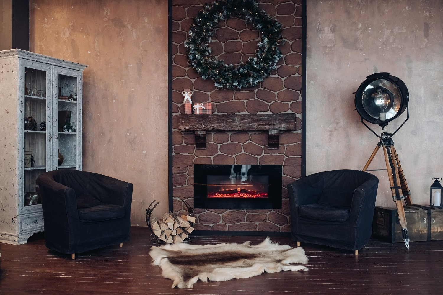 Christmas interior decorated with Christmas wreath made of fir branches. Two armchairs and a genuine animal fur on the floor in front of an electric fireplace.