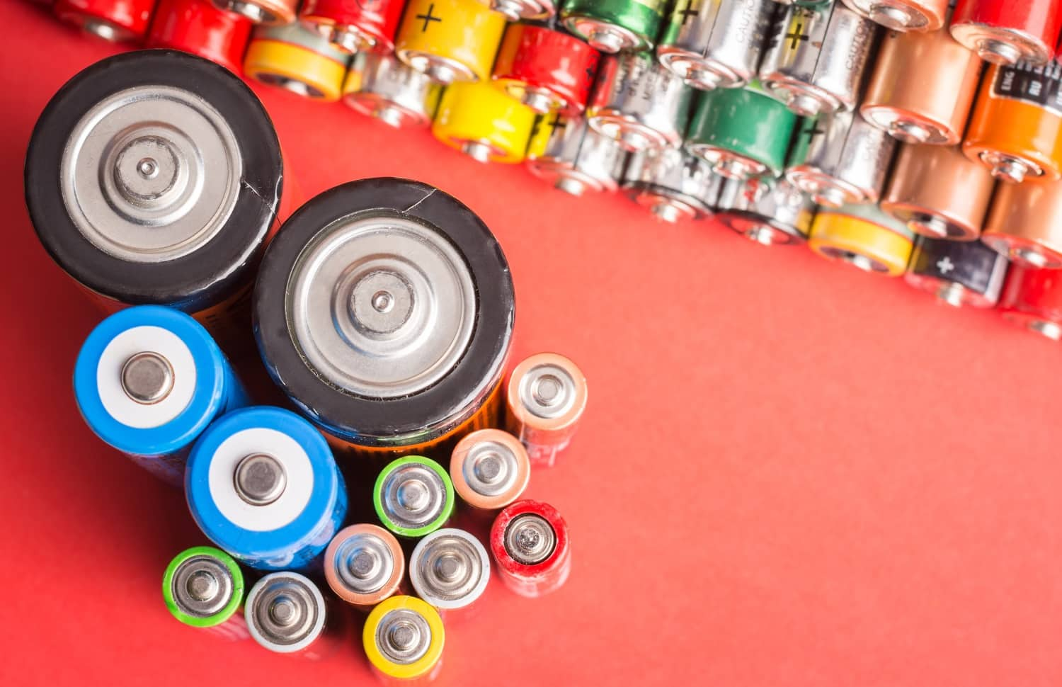 Batteries of different types and sizes on red background