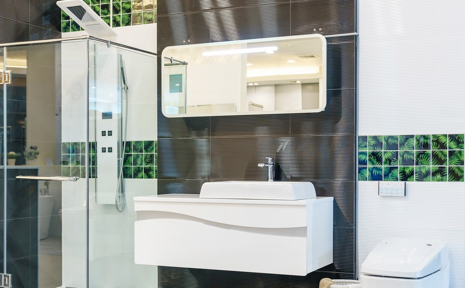 Spacious and bright modern bathroom interior with white walls, a shower cabin with glass wall, a toilet and faucet sink