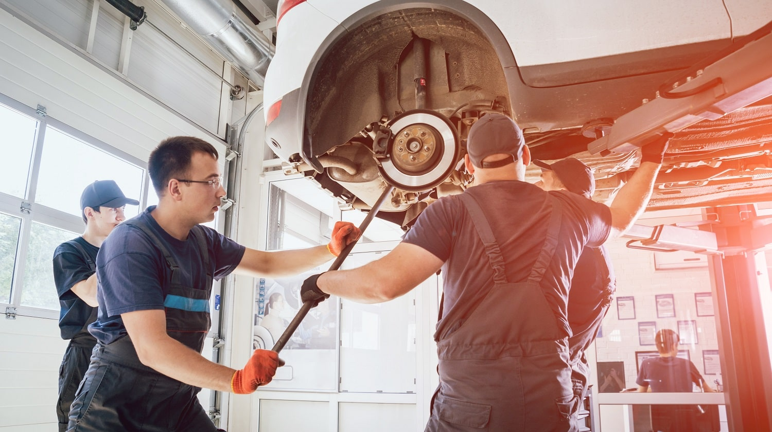 Car mechanics repair car suspension of lifted automobile at repair service station. Background