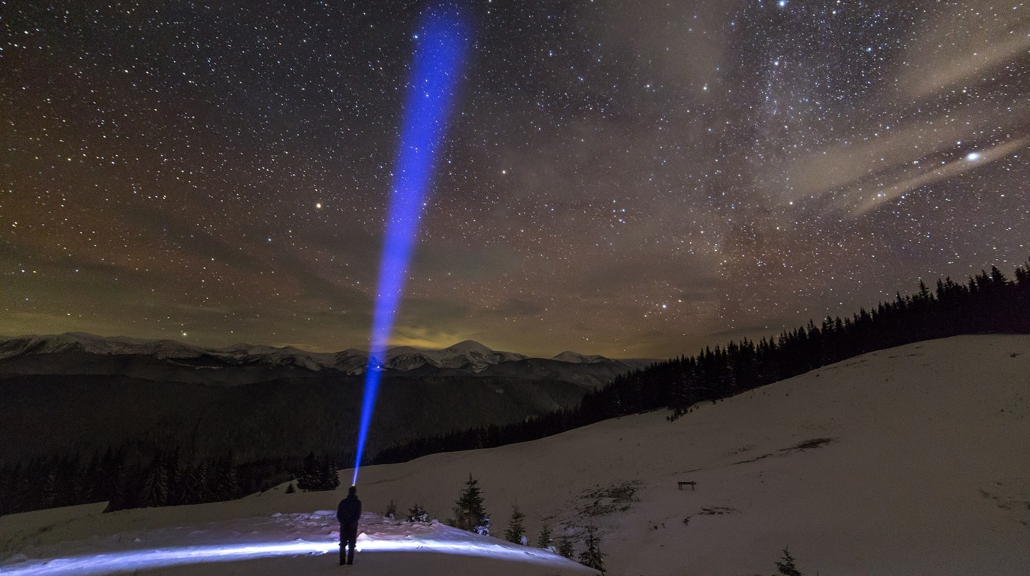 Back view of man with head flashlight standing on snowy valley under beautiful dark blue winter starry sky, bright blue beam on stars and mountains ridge background. Night photography, light painting.