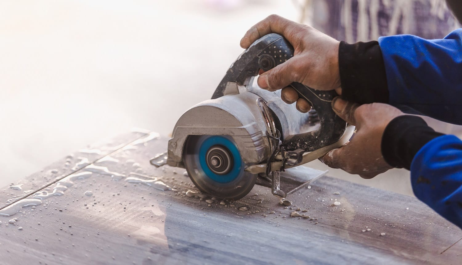 Man professional worker cutting tile with circular saw electric construction interior.