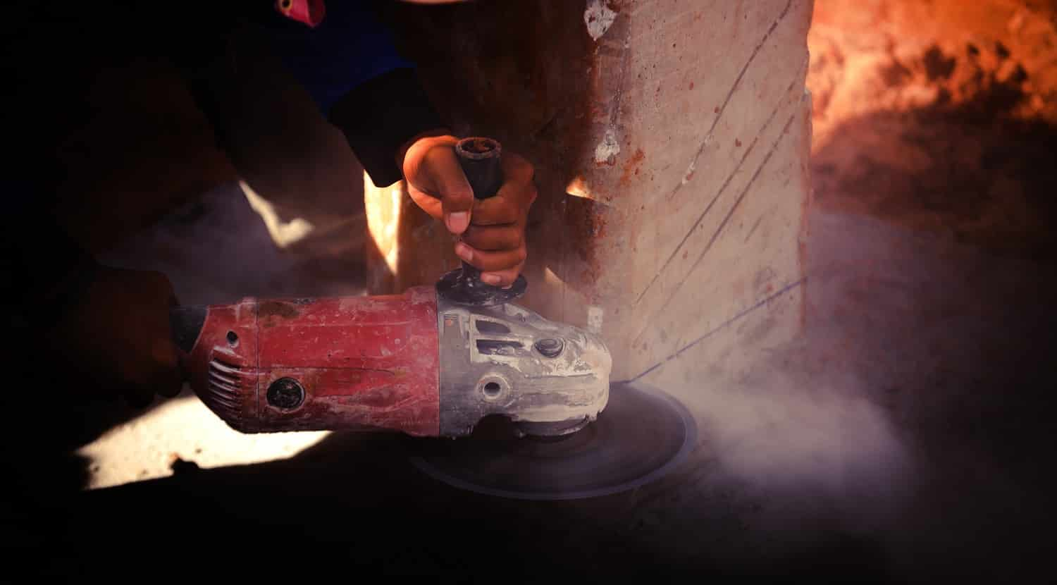 Industry construction labor men worker holding electric saw cuting concrete