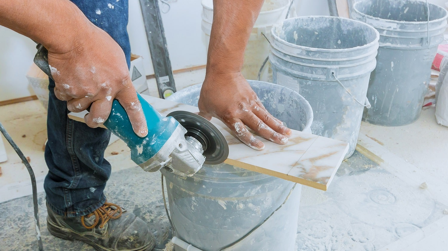 A construction worker cutting a tile using grinder round the ceramic disc