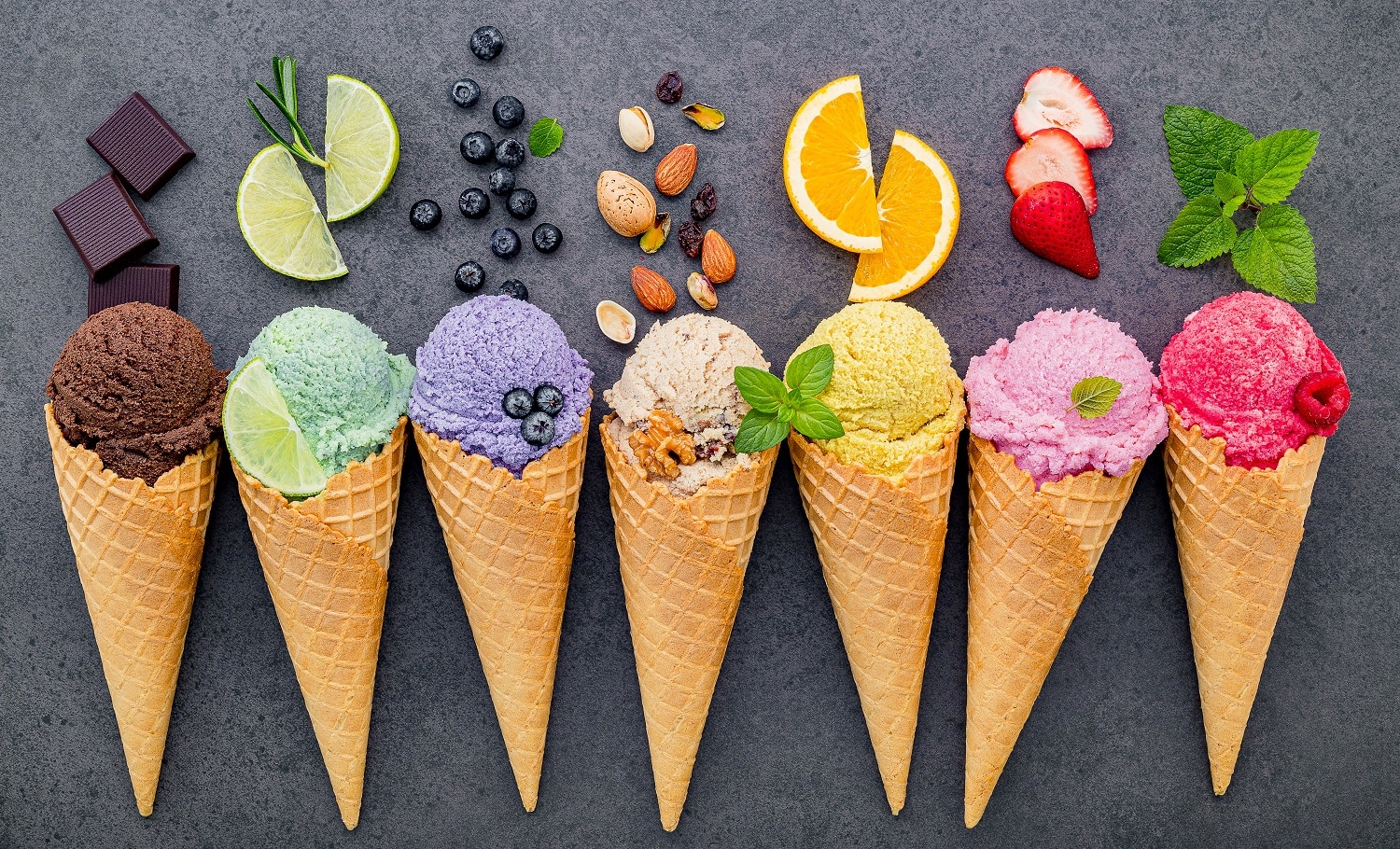 Various of ice cream flavor in cones blueberry ,lime ,pistachio ,almond ,orange ,chocolate ,vanilla and coffee set up on dark stone background . Summer and Sweet menu concept.