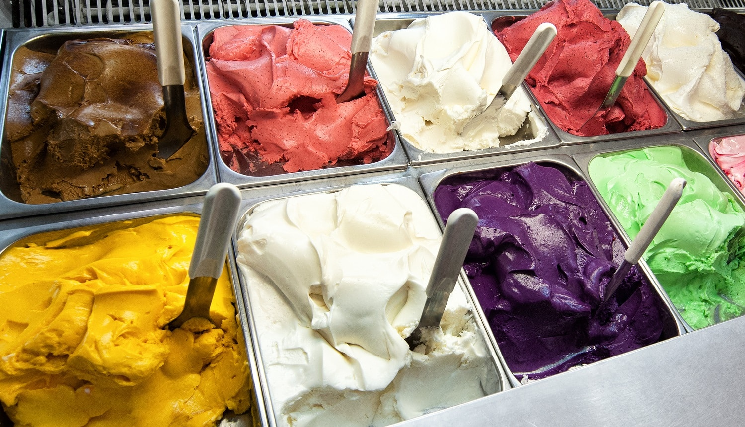 Colorful display of an assortment of freshly made different fruity flavoured Italian ice cream in the window of an ice cream parlour or shop for sale as takeaway desserts