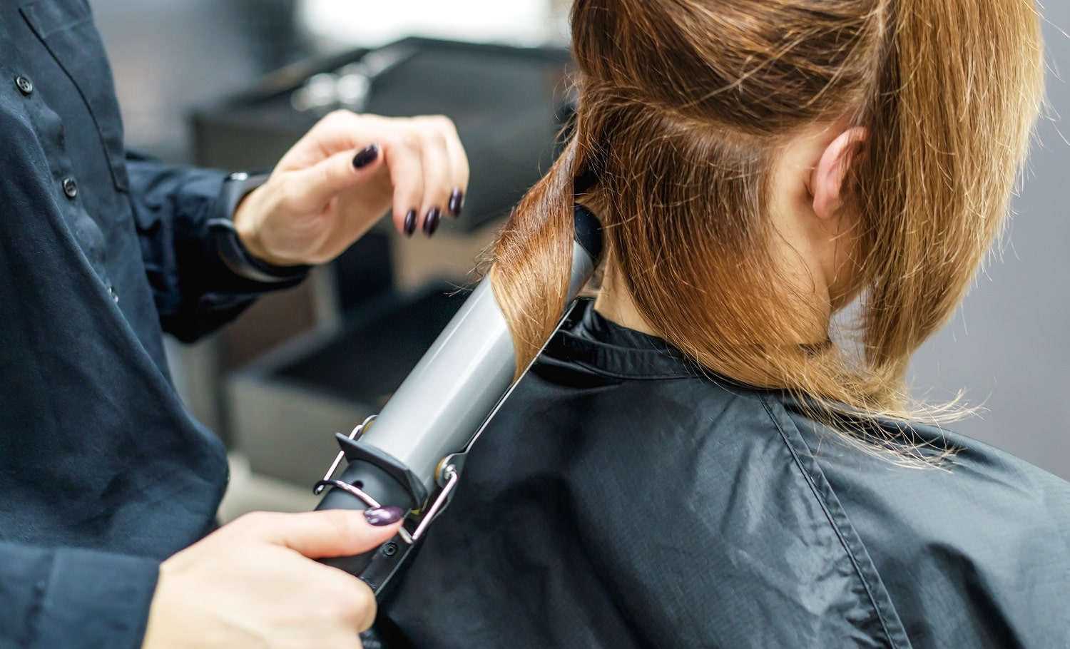 Hairdresser hand is curling women's hair with iron in beauty salon close up.