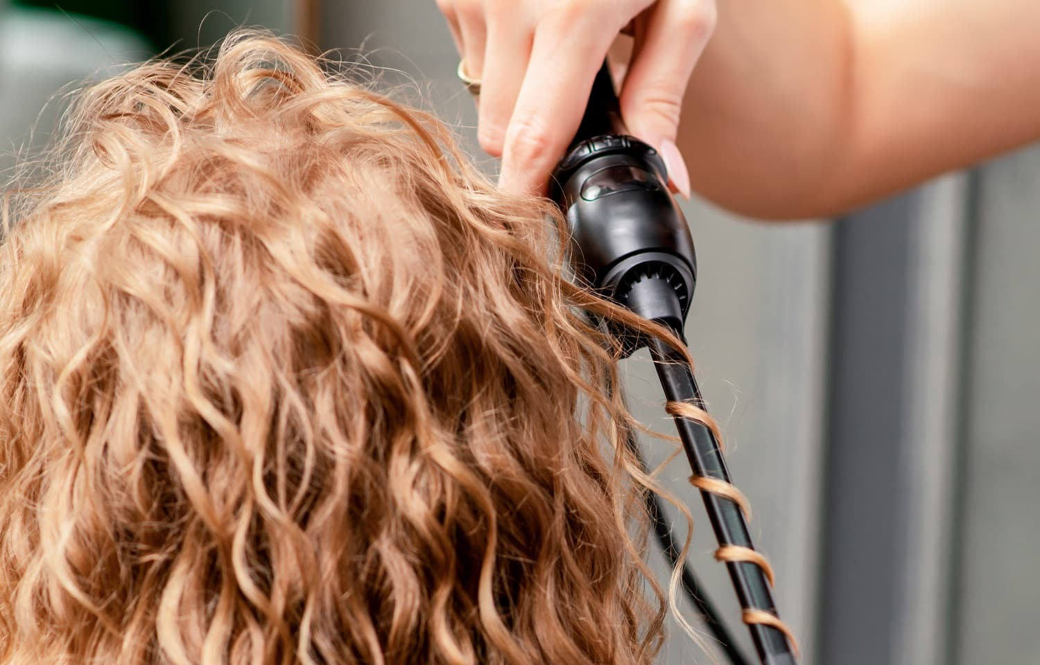 Hairdresser hands curl woman's hair by curling iron in salon.