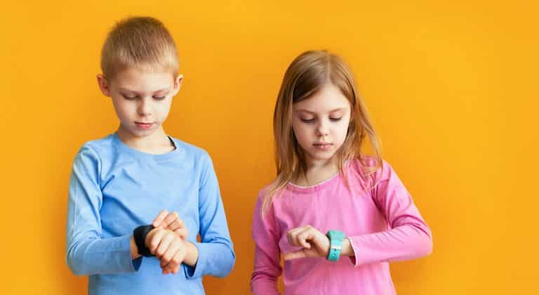 Happy children 6-8 years old with a smart GPS watch talking to parents safely. orange background