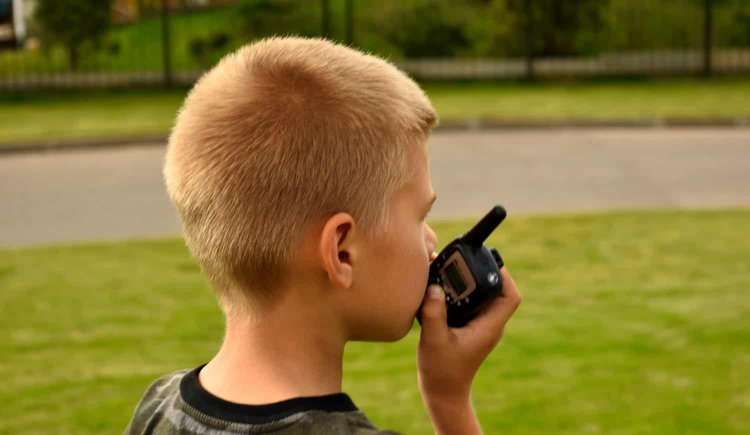 Children's toy walkie-talkie in hand. The child plays in the fresh air.