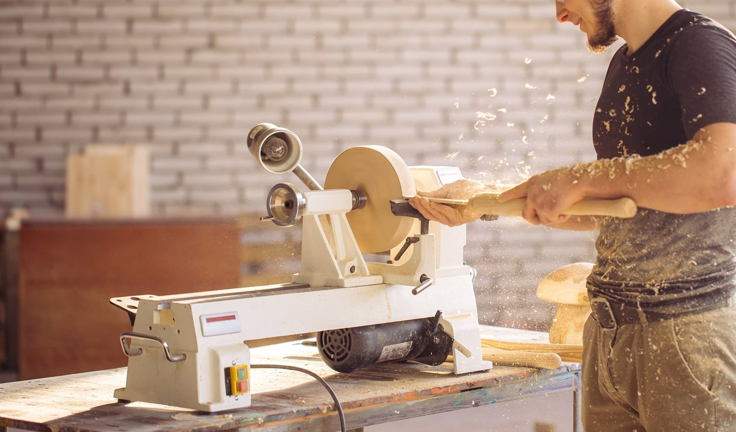 Young carpenter processing wooden plank on special woodworking machine