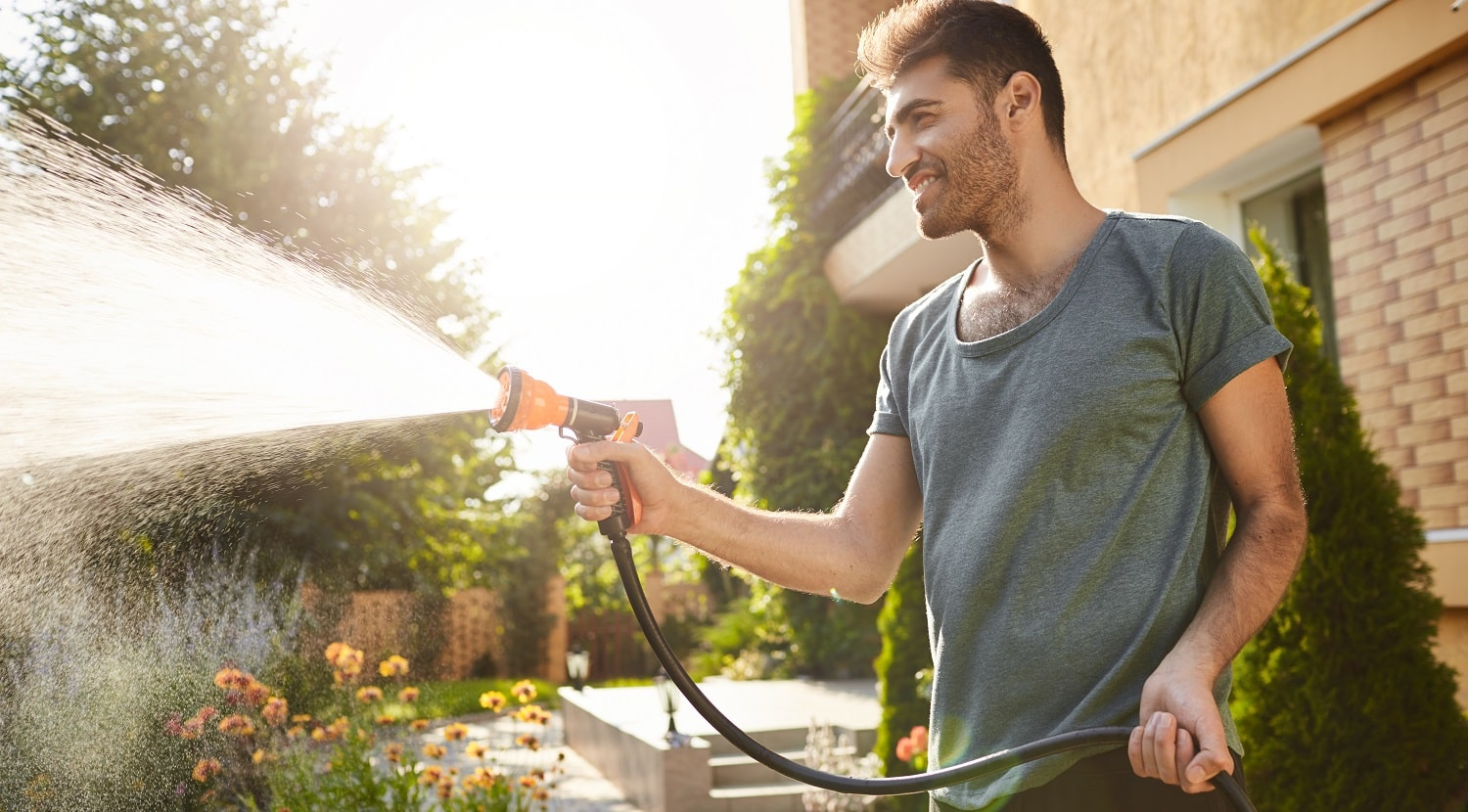 Summer morning in countryside house. Portrait of young attractive tan-skinned bearded man in blue t-shirt smiling, watering plants with hose, working in garden
