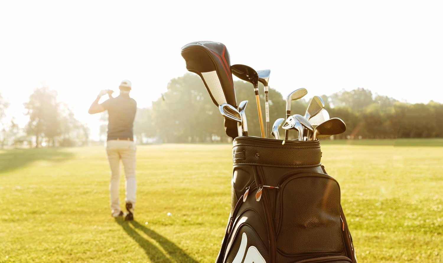 Back view of a male golfer swinging golf club and following shot in the air