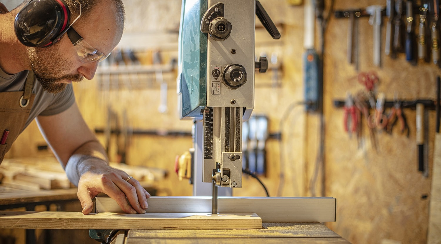 portrait of a carpenter inside his carpentry workshop using a band saw. Wear ear and eye protection