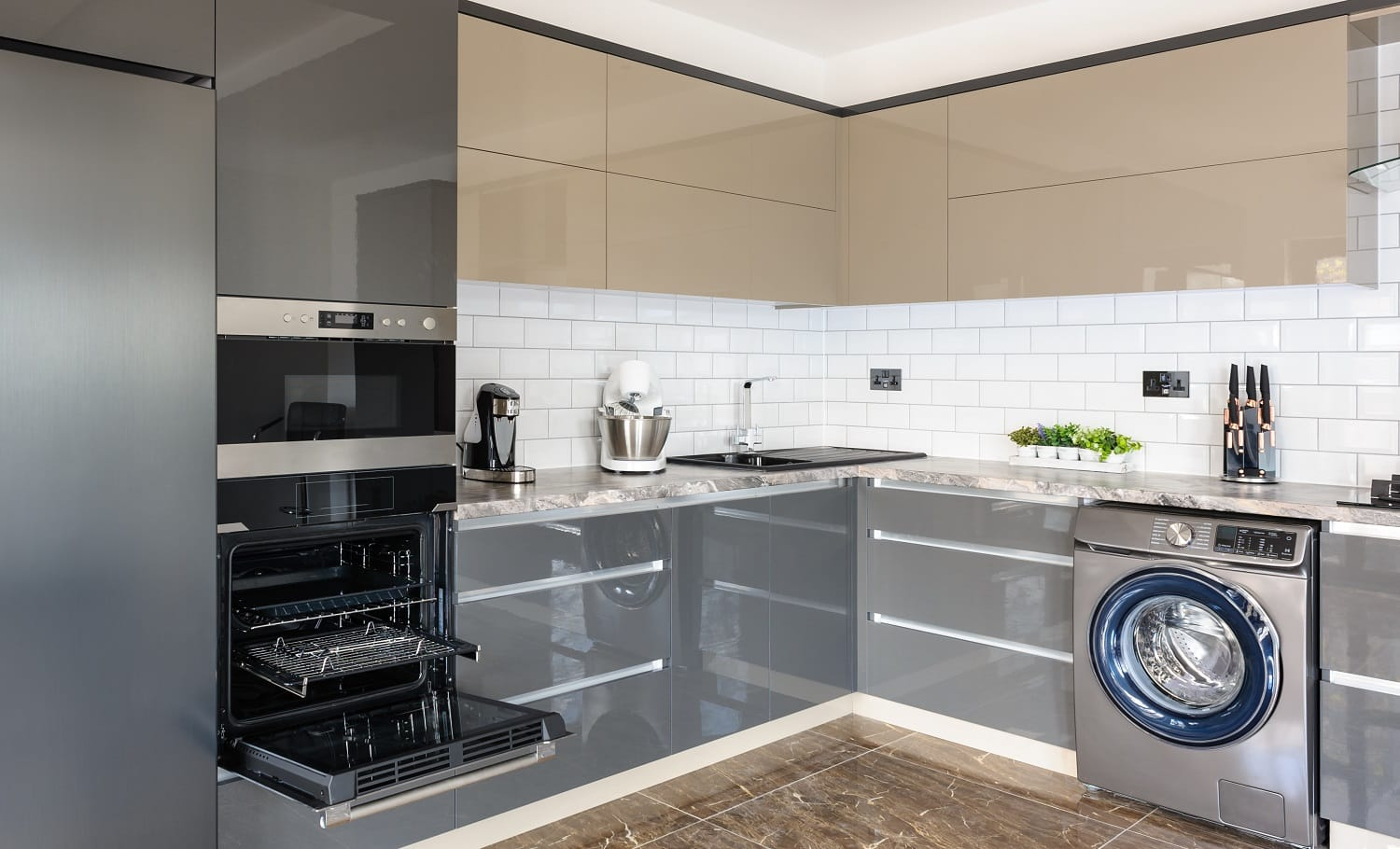 Spacious luxury well designed modern grey, beige and white kitchen with marble tiles floor. some lockers and door of electric oven are open