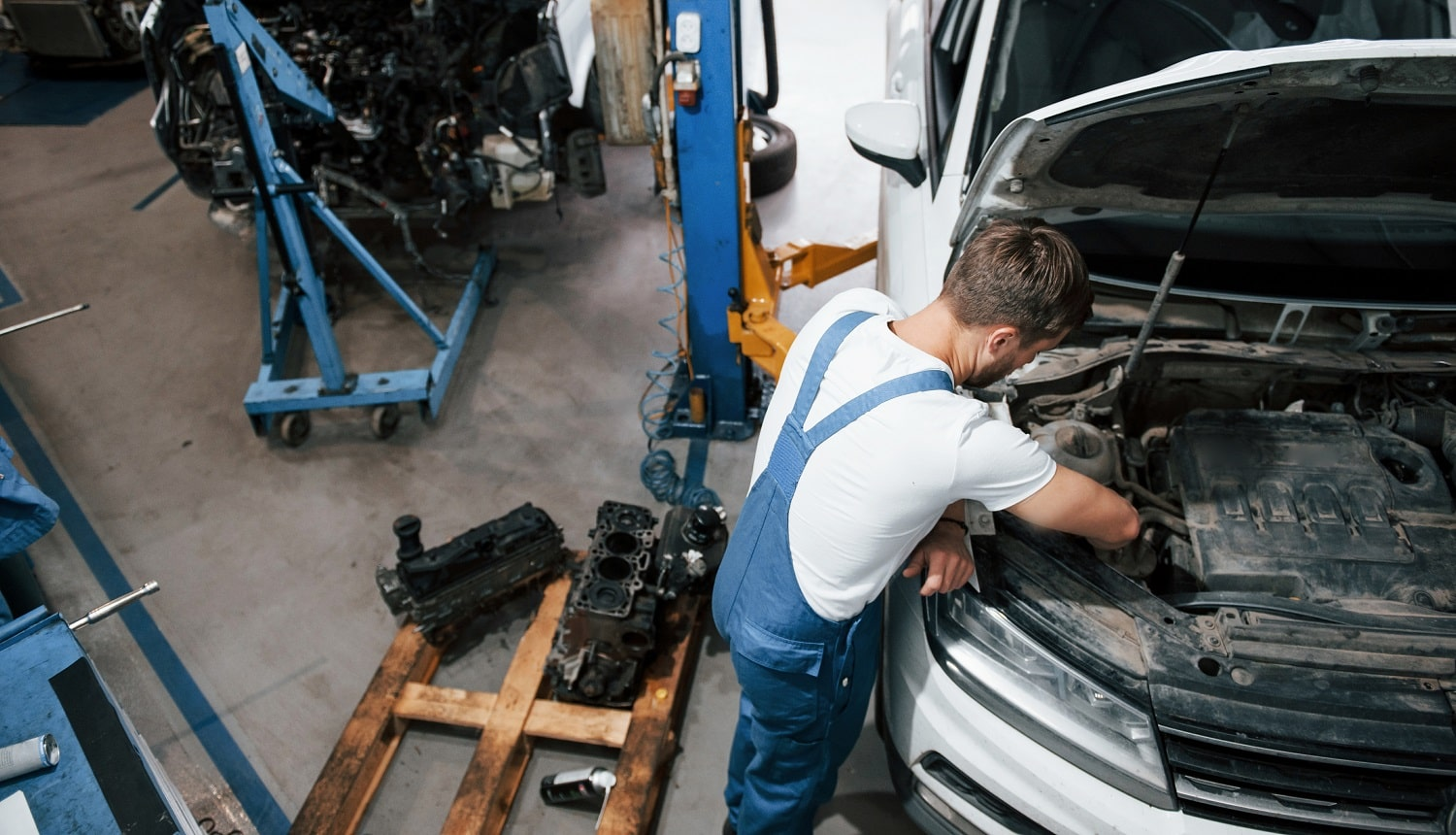 Luxury white car. Employee in the blue colored uniform works in the automobile salon.