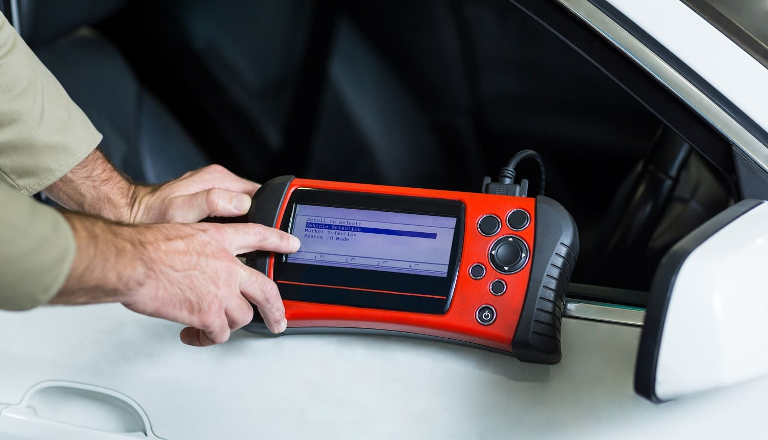 Hands of mechanic using a diagnostic tool in repair garage