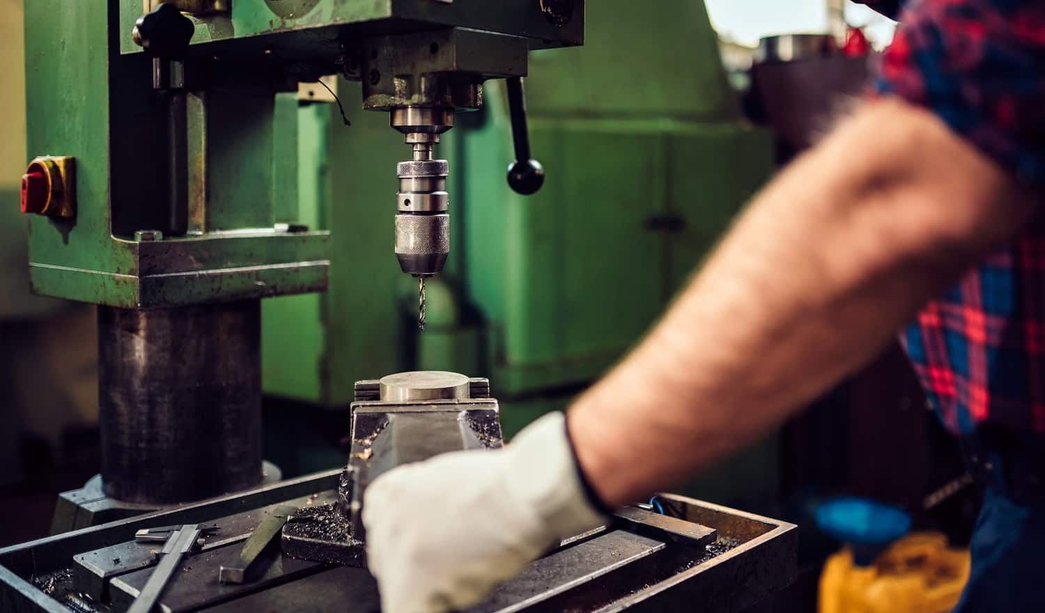 Close up photo of worker using drill press in the industrial factory