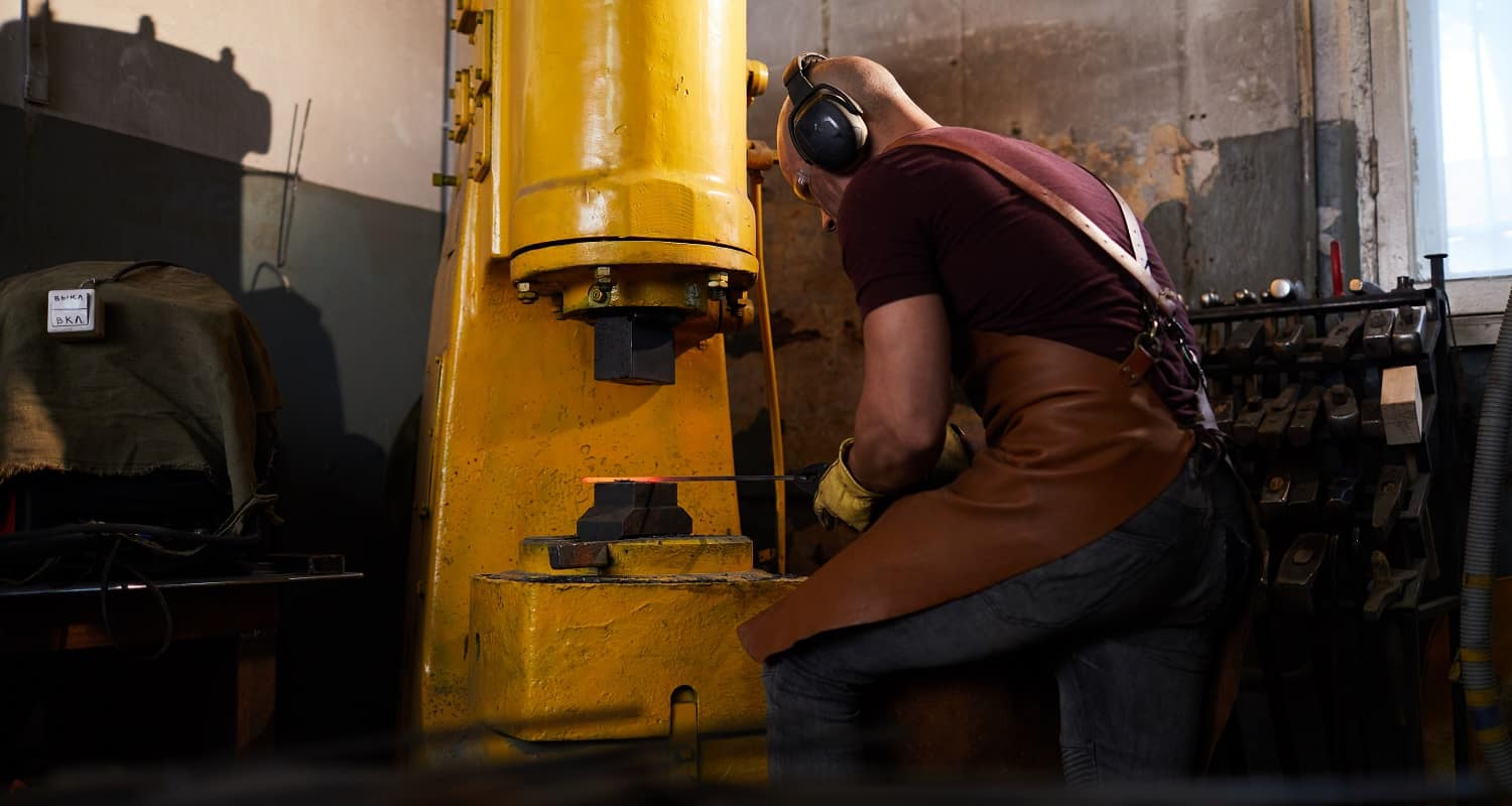 Concentrated skilled man in apron and ear protectors putting metal bar under press while working with hydraulic forging press