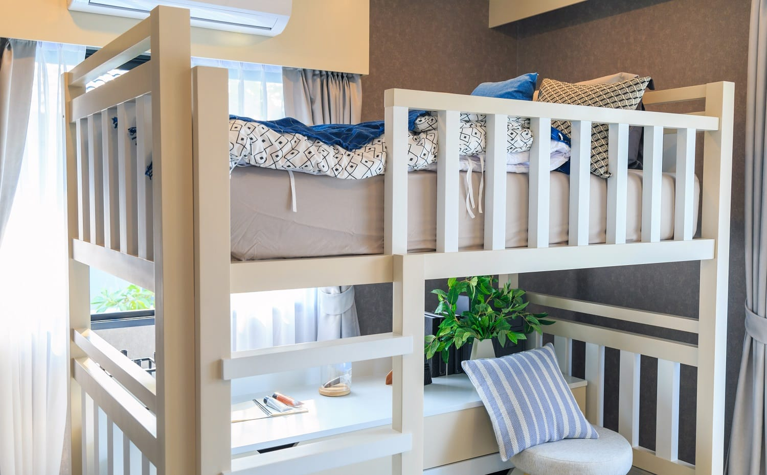 A white wooden bunk bed with a pillow and air conditioner in a children's bedroom with warm light from a window.
