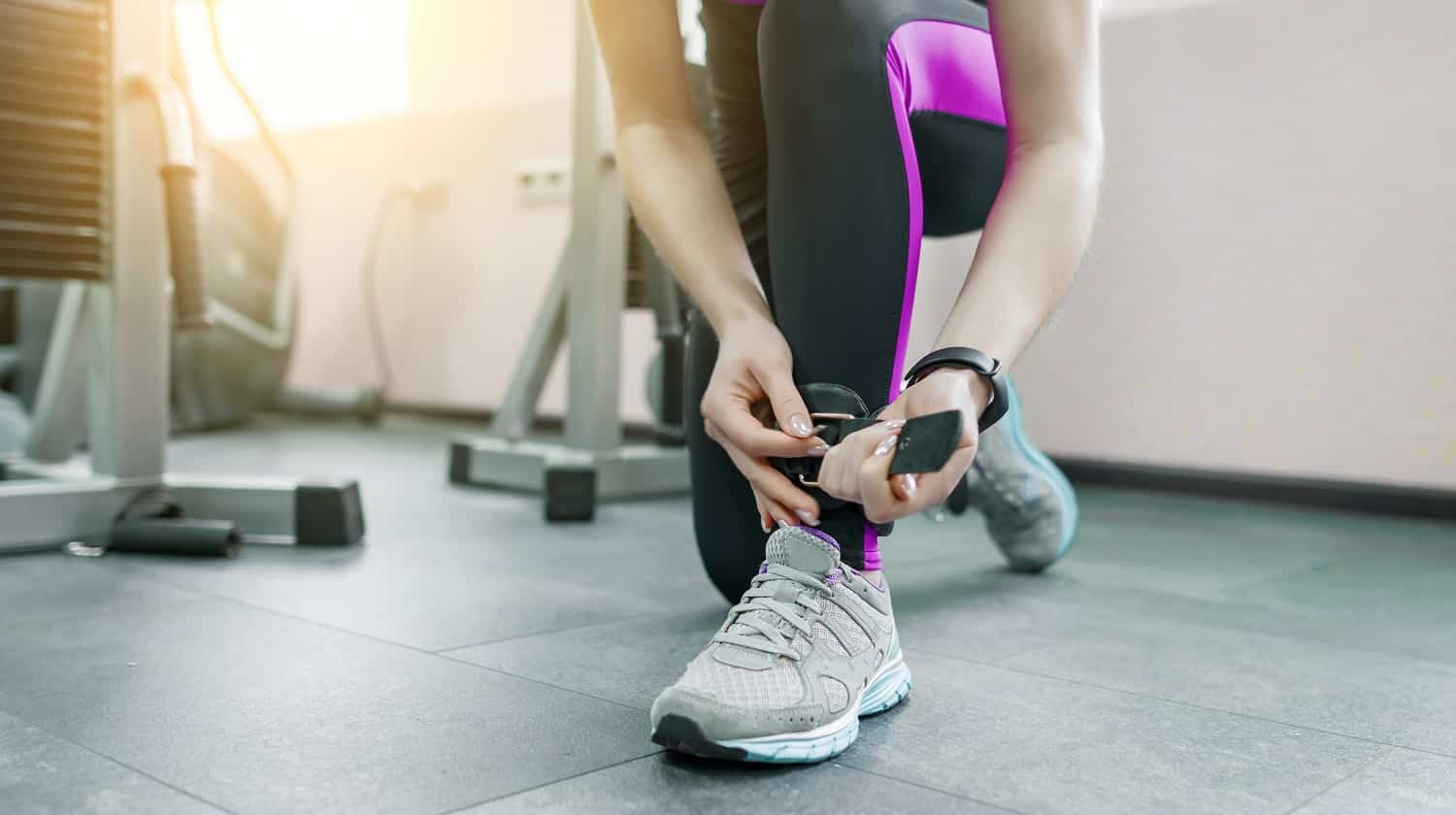 Young woman wearing leather ankle straps prepares to exercise on fitness machine in the gym. Fitness, sport, training, people concept