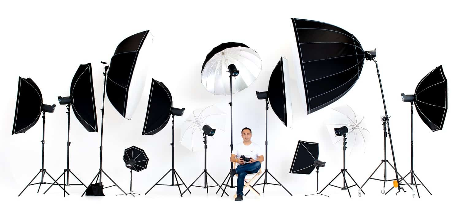 Asian photographers sit on the director's chair with flash studio lights a lot of patterns around on a white background.