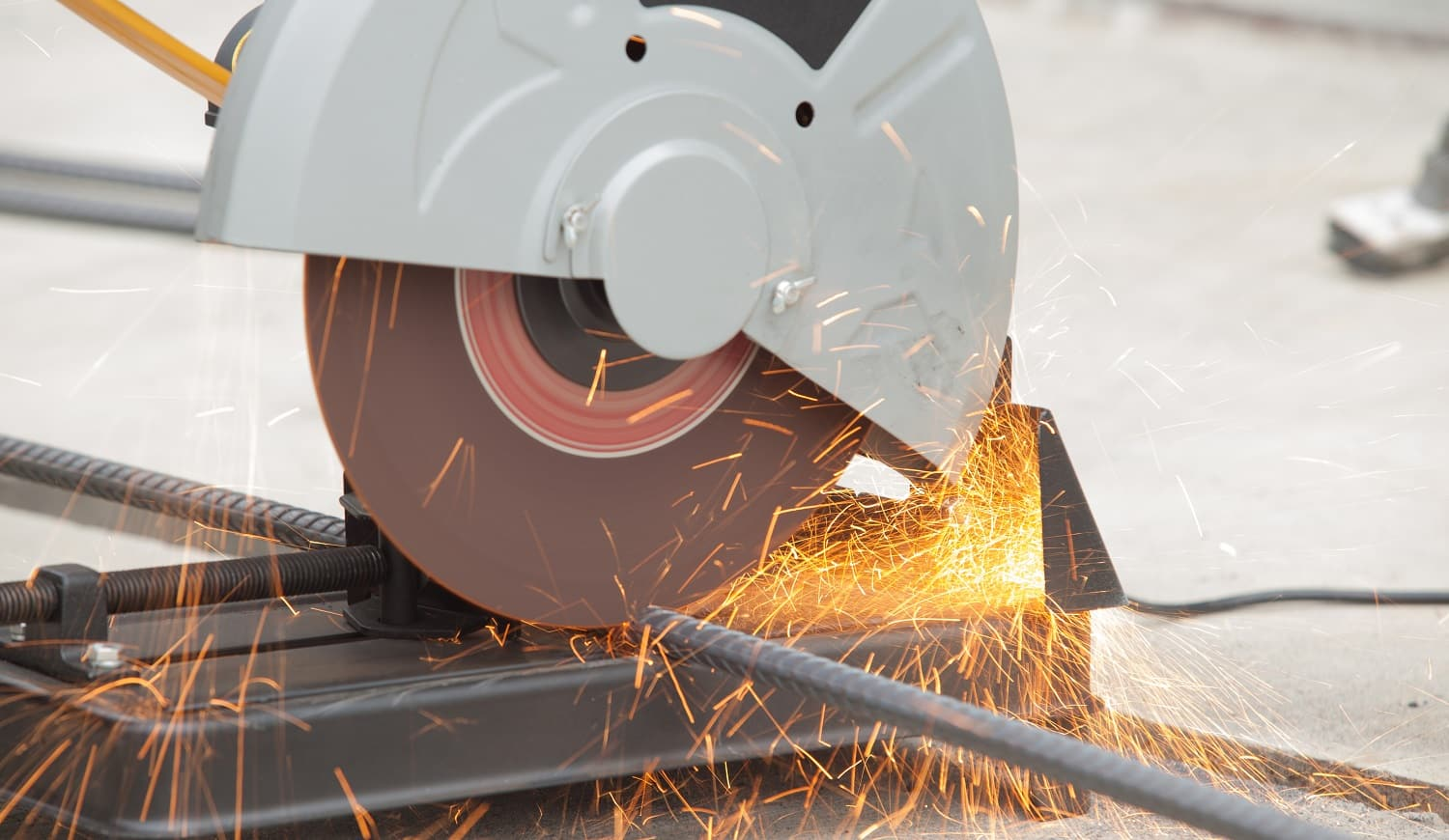 Close up of rebar being cut at a construction site. Short trail of sparks