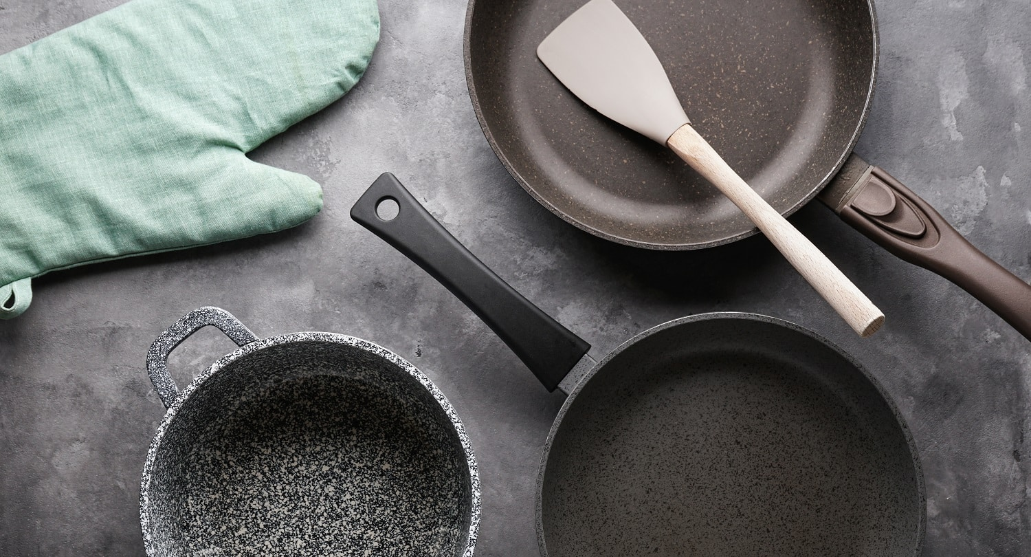 Set of pans. Various kitchen utensils on a gray table background, close-up.