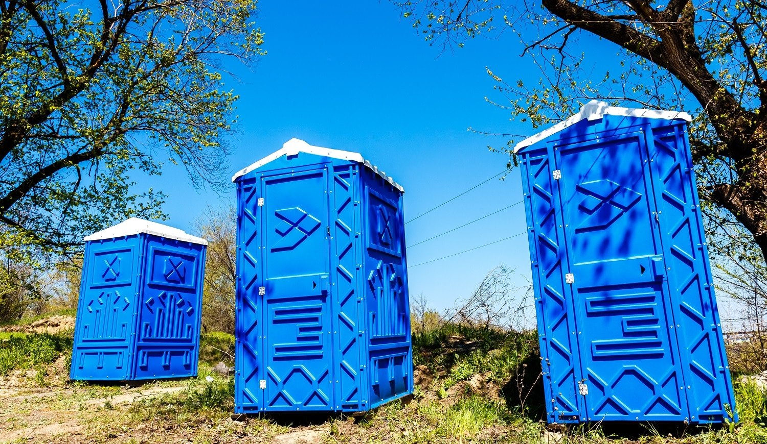 Three Blue Cabines Of Chemical Toilets In a Park at sunny Summer Day.