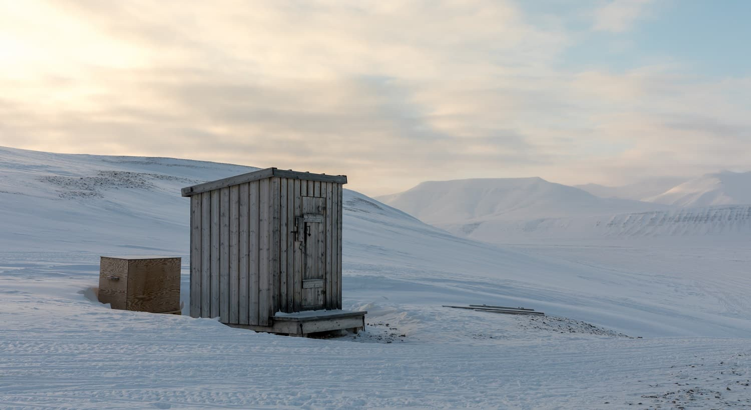 Isolated small shed in the middle of huge mountains covered by snow in the arctic landscape at Svalbard, Norway