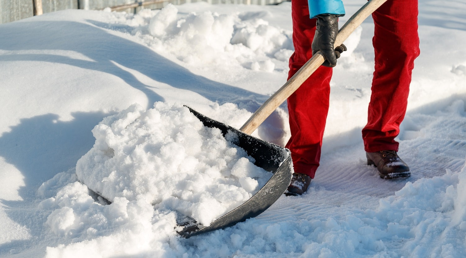 girl cleans snow shovel on the site near his house. sunlight day