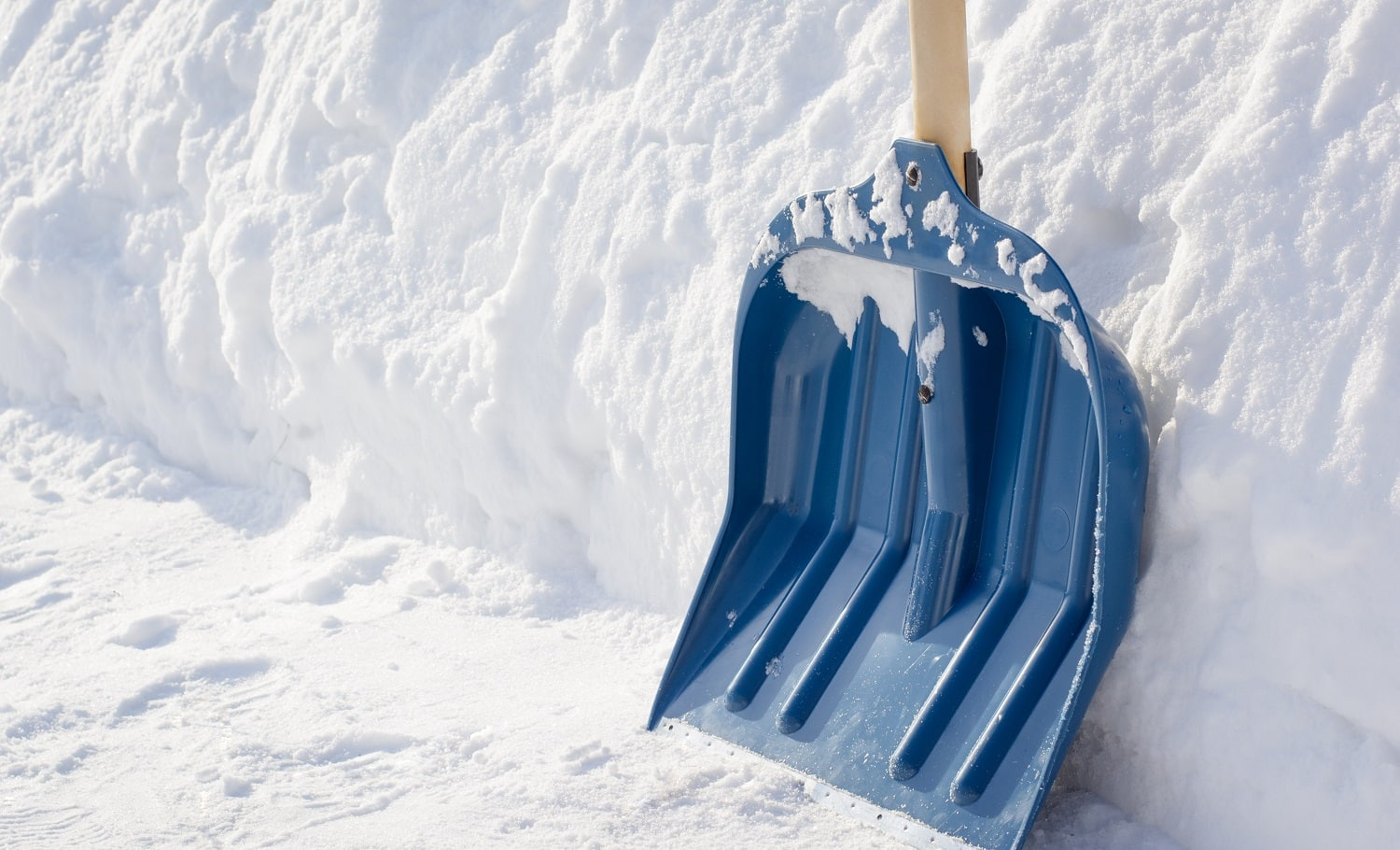 Snow shovel with a wooden handle after cleaning sidewalk in the street