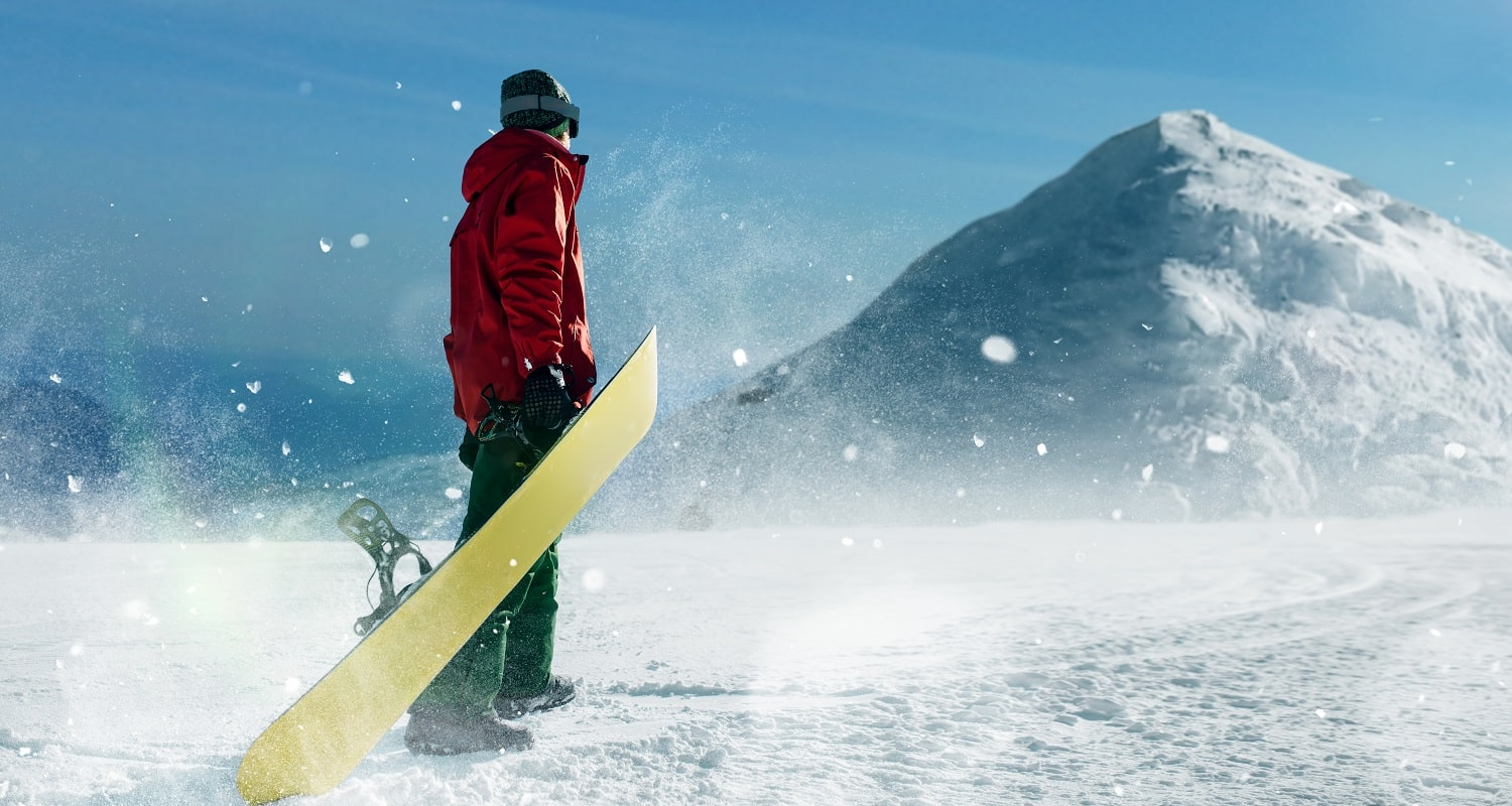 Snowboarder holds board in hands, blue sky and snowy mountains on background. Winter active sport, extreme lifestyle, snowboarding