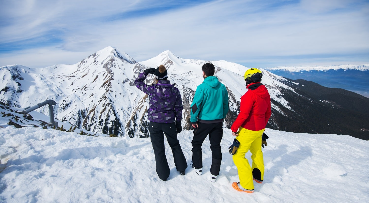 Rear view of young people enjoying in snowy winter on the top of the mountain with amazing background look.