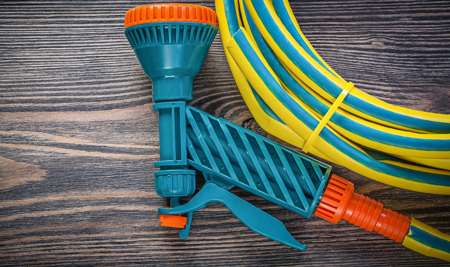 Coiled rubber hose water sprayer on wooden board gardening concept.
