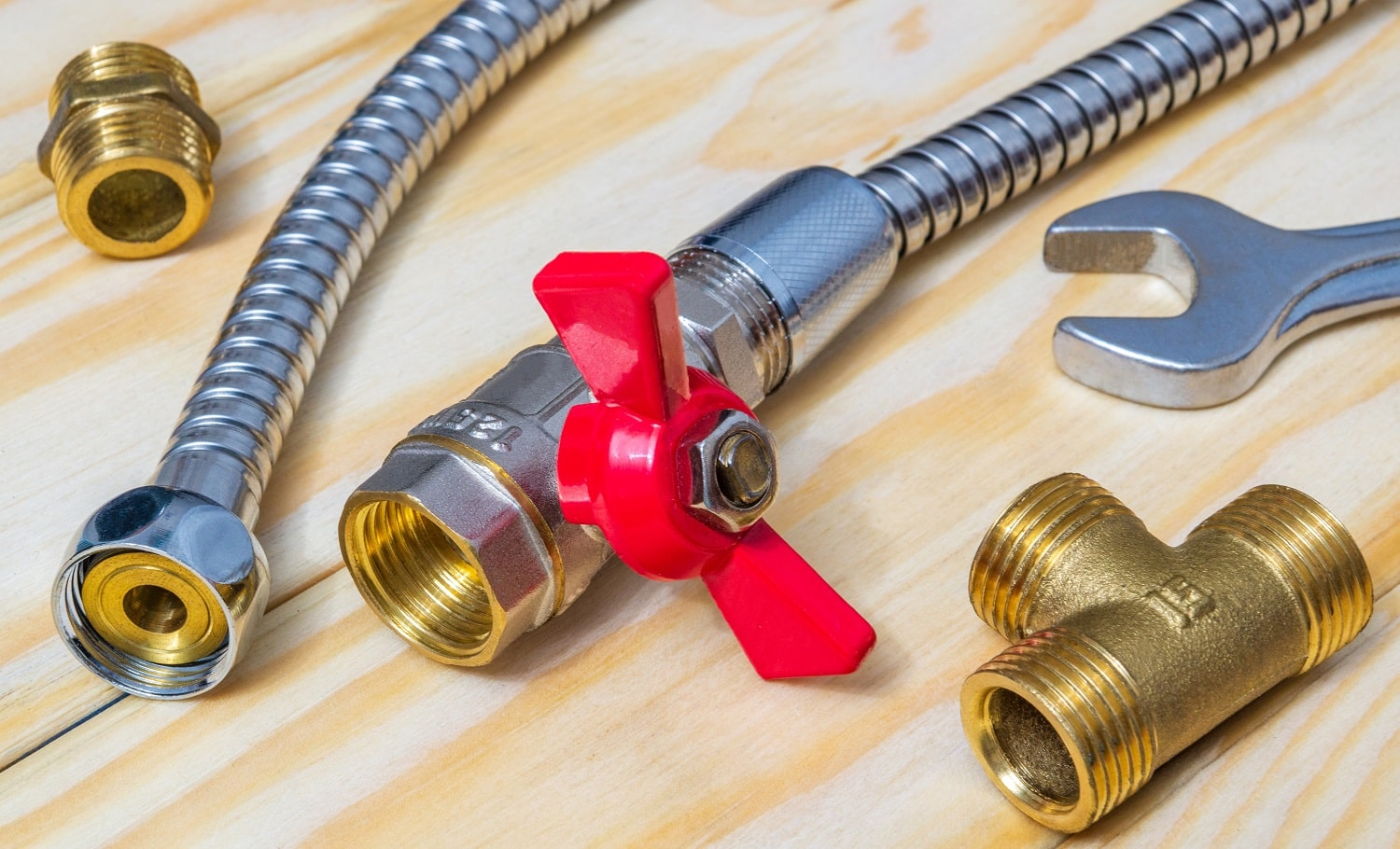 Metal ball valve with a red handle with fittings and hose prepared for repair on wooden boards