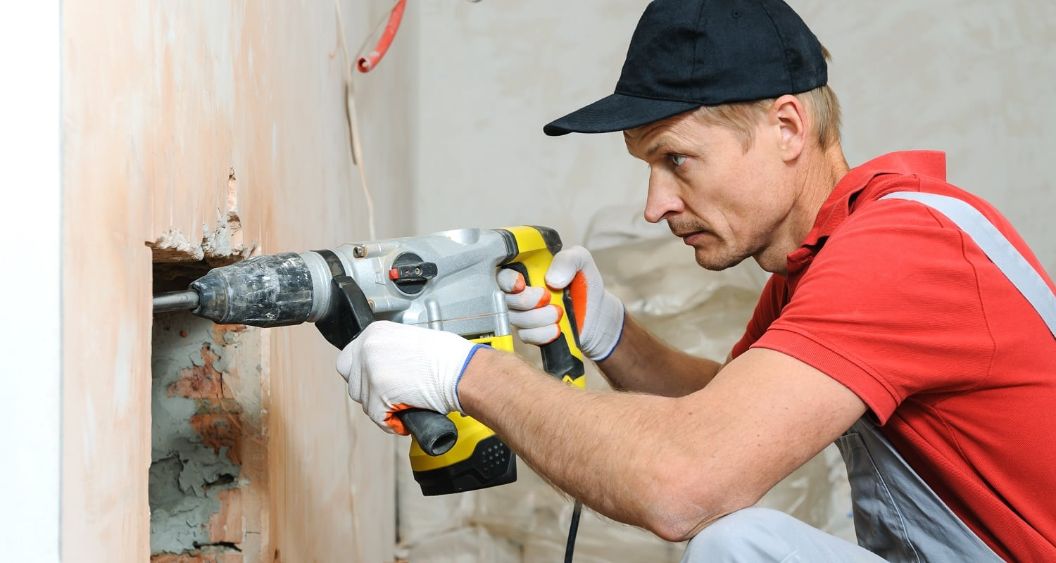 Worker with an electric hammer. Man makes niche in the brick wall.