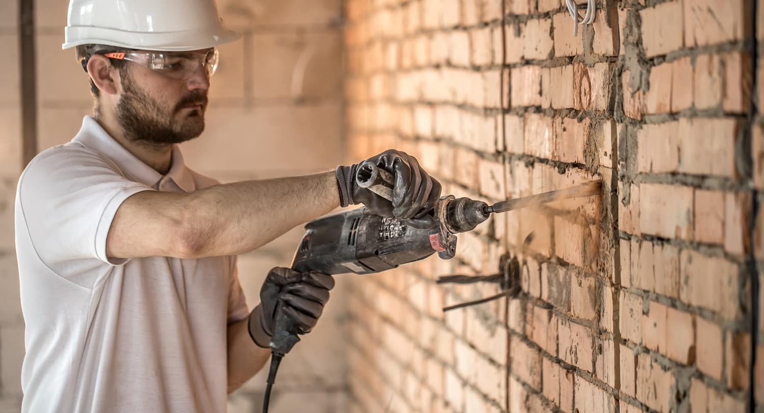 Handyman uses jackhammer, for installation, professional worker on the construction site. The concept of electrician and handyman. House and house reconstruction.