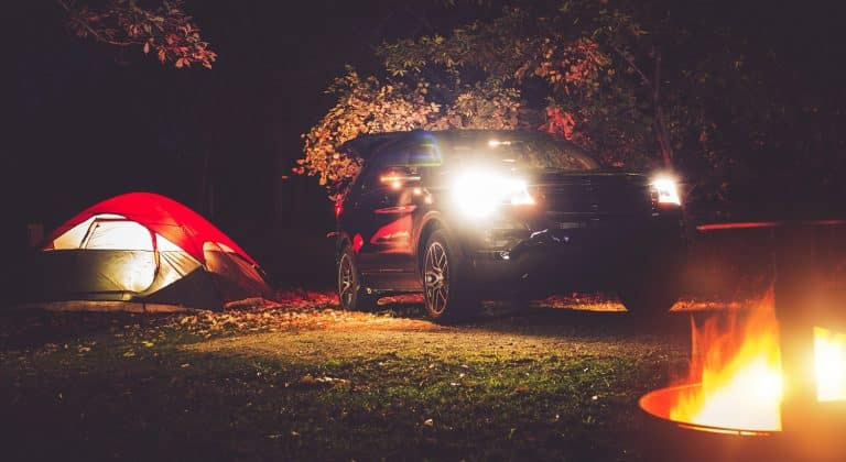 Camping Adventure. Tent Camping in the Deep Forest. Modern Offroad Car, Tent and Burning Wood in the Camping Fire Pit. Outdoor Adventures.