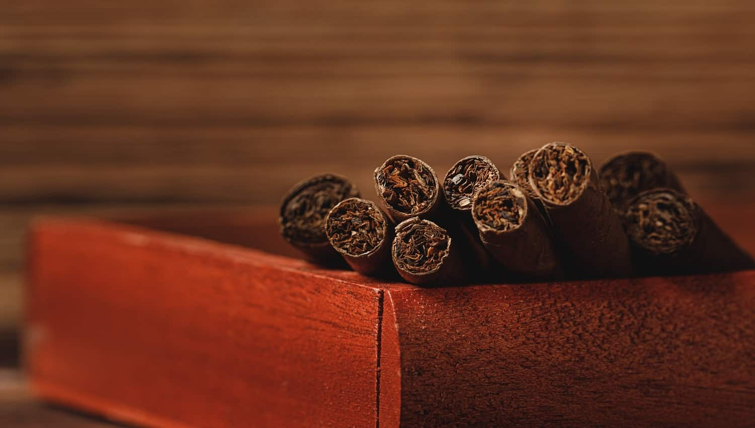 Red wooden box with new rolled cigars on wooden table close up